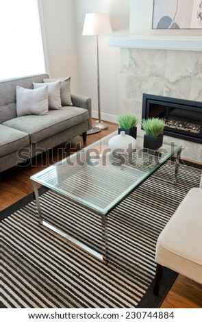 Sofa, couch with some pillows, nicely decorated coffee table and two chairs. Fragment of living room.  Interior design. Vertical. - stock photo