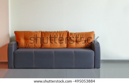 Sofa, interior design, office. Empty waiting room with a modern gray sofa with yellow cushions in front of the door and a clock on the wall