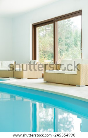 Sofa next to the swimming pool in expensive house - stock photo