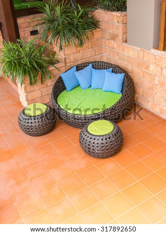 sofa weave Rattan stick chair with blue pillows on orange tile and old brick wall - stock photo