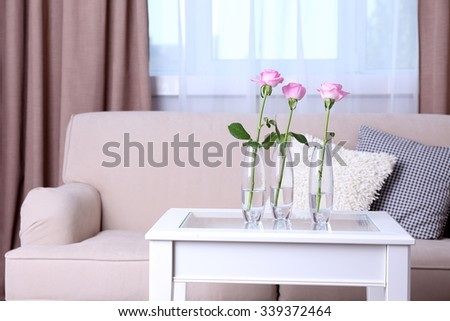 Sofa with beautiful pillows and focused vase with flowers on the table in front of it in the room - stock photo