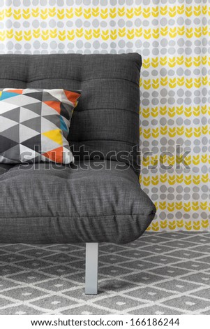 Sofa with colorful cushion, on bright floral background. - stock photo