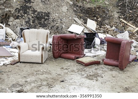 Sofas broken and abandoned, detail of furnishings from left, dirt and debris - stock photo