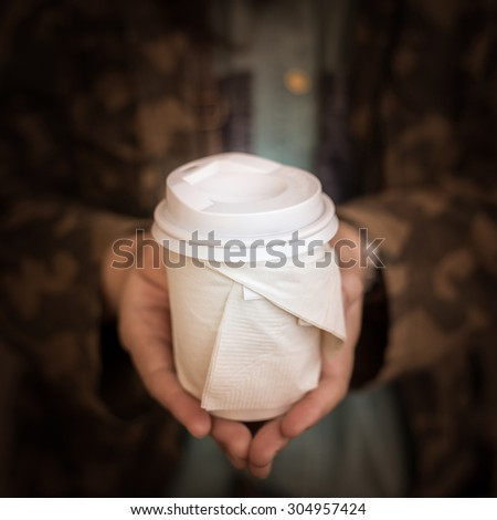 sofe focus of the woman hand serving the cup of hot coffee - stock photo