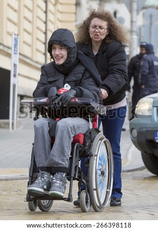 Sofia, Bulgaria - April 3, 2015: A mother and her son are going to a protest with other parents and relatives of physically disabled children and adults against discriminatory state laws.