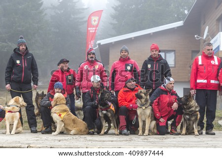 Sofia, Bulgaria - April 20, 2016: Men and their dogs at the search and rescue team at Bulgarian Red Cross are posing for a group picture in the mountain.