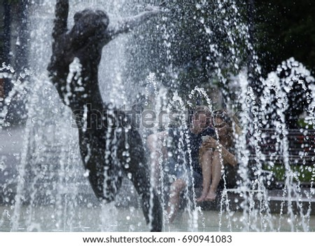 Sofia, Bulgaria - August 6, 2017: Man and woman cool in a fountain in the city center