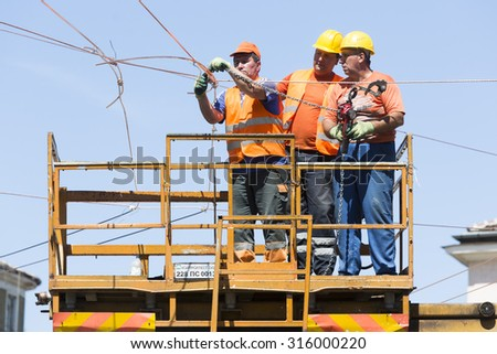 Sofia, Bulgaria - August 18, 2015: Three elecrticity construction workers on a platform are repairing tram's wires.
