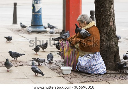 Sofia, Bulgaria - February 27, 2016: A homeless beggar woman is covered by pigeons while begging at a street in Sofia. Bulgaria is still the poorest EU country. - stock photo