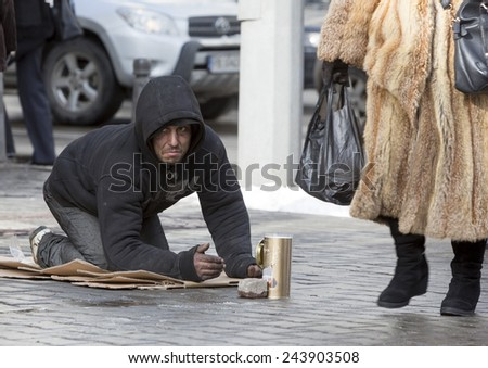 Sofia, Bulgaria - January 12, 2015: A homeless begger is begging on a busy street in the center of Sofia. - stock photo