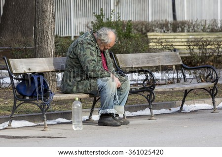 Sofia, Bulgaria - January 8, 2016: A homeless man is sitting and sleeping on a bench in a park in Bulgaria's capital Sofia. The country is still struggling with great poverty among its citizens. - stock photo