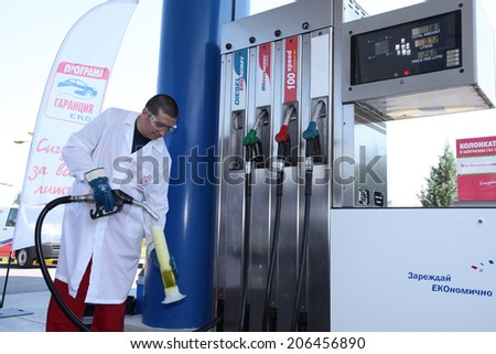 Sofia, Bulgaria, July 17, 2014 An inspector takes sample of gasoline at gas station to check the quality of the fuel. - stock photo