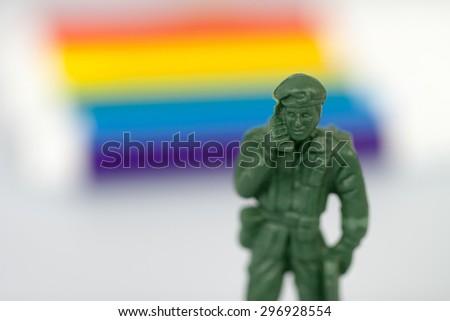 Sofia, Bulgaria - July 16, 2015: Plastic toy soldier casting model figure shot on blurred rainbow background, symbolizing mocking attitude to military power - stock photo