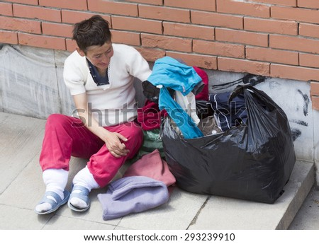 Sofia, Bulgaria - June 25, 2015: Homeless woman with her possessing is sitting at an entrance of the subway underpass near the Central Station in Sofia, Bulgaria. - stock photo