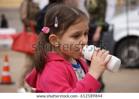 Sofia, Bulgaria - March 04, 2017 - Little girl, dressed in pink drinking from a bottle