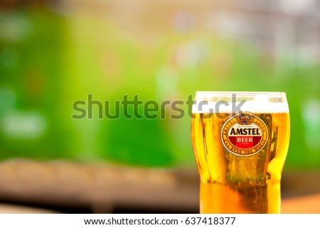 SOFIA, BULGARIA - MAY 08, 2017:Close-up Amstel glass full of beer - background of tv .Amstel Premium Pilsener is an internationally known brand of beer produced by Heineken International