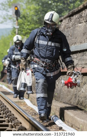 Sofia, Bulgaria - May 19, 2015: Firefighters are approaching a chemical cargo train crash near Sofia, Bulgaria. Teams from Fire department are participating in a training with spilled toxic materials.