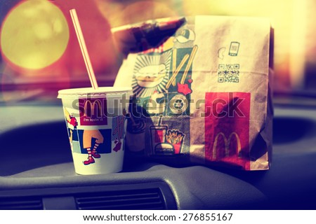 SOFIA, BULGARIA - MAY 9, 2015: McDonalds Mcdrive meal in vintage car, modern filtered look, abstract city bokeh background.Is the world's largest fast food chain, over 31,000 restaurants worldwide.