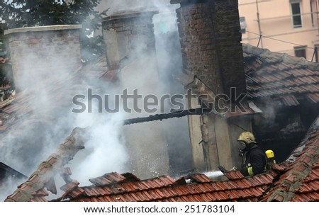 Sofia, Bulgaria - November 24, 2012: Firefighters are extinguishing fire on a burning house roof.