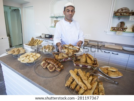 Sofia, Bulgaria - November 17, 2014: Gypsy baker shows freshly prepared bread, croissants, cookies, pancakes and pretzels at the restaurant for fast food in the city center.