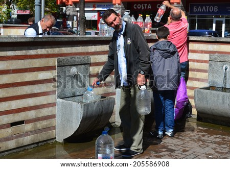SOFIA BULGARIA SEPT 25: Locals fill bottles with mineral water that flows from hot springs beneath the city. On sept. 25 2013 in sofia Bulgaria