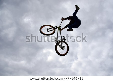 Sofia, Bulgaria - September 23, 2017: Back lit dark silhouette of a young boy - freestyle stunt cyclist - flying in the sky with his bike, performing a trick - jump from a skate-park ramp