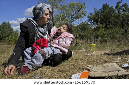 SOFIA, BULGARIA, 20 SEPTEMBER 2013 - Unknown Syrian mother, holding her sick child is sitting on the grass near a refugee camp in Sofia, Bulgaria.  - stock photo