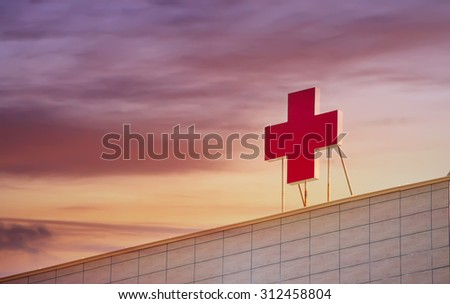 SOFIA - SEPTEMBER 02 , 2015 : Sunset over the medical red cross on the top of the popular hospital Pirogov in Sofia, Bulgaria  - stock photo