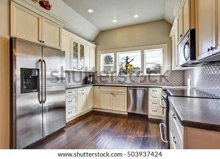 Soft beige kitchen cabinets , built-in stainless steel refrigerator , dark tones hardwood floor and vaulted ceiling in a kitchen room. Northwest, USA