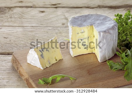 soft blue cheese from France with wedge portion and some herbs on a rustic wooden table - stock photo