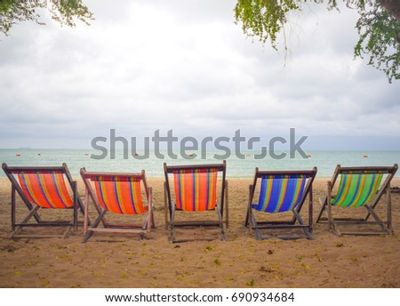 Soft blue sea and colorful sand beach with beach chairs