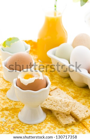 Soft boiled egg in egg cup and served with toast fingers.
