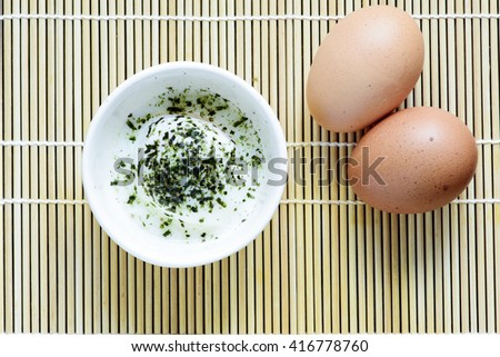 Soft boiled or Onsen egg with seaweed on Japanese bamboo sheet with chopstick - stock photo