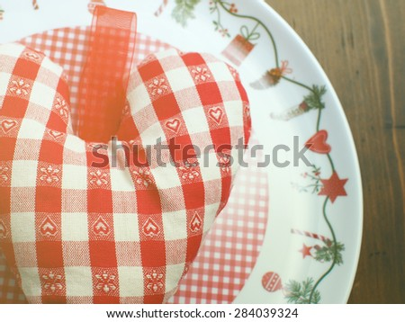 Soft checkered red and white heart on christmas plate and on brown wooden table