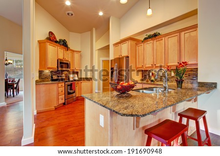 Soft colors modern kitchen area with wooden storage cabinets, steel appliances and tile back splash trim - stock photo