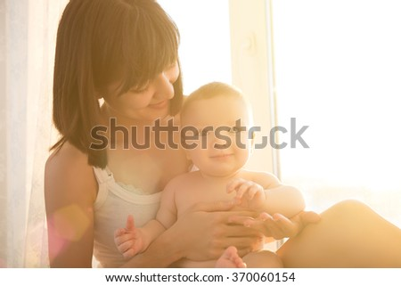 Soft comfort photo young mother with baby at home in white room near window - stock photo