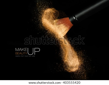 Soft cosmetics brush releasing a cloud of glowing sparkling face powder over a black background with copy space in a beauty and makeup concept - stock photo