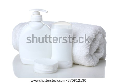 soft cotton pads neatly stacked and folded with a soft bath towel about cosmetic container with liquid soap and a deodorant stick container. Design white plastic bag isolated on white background - stock photo