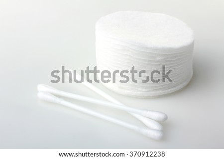 soft cotton pads neatly stacked in a pile and cotton swabs isolated on white background - stock photo