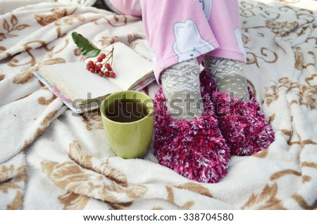 Soft cozy photo of slim tan woman in warm sweater on the bed with cup of tea in hands, top view point.Composition with warm plaid, book, cup of hot drink and female legs