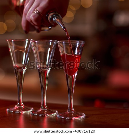 Soft drink being poured into three cocktail glasses - stock photo