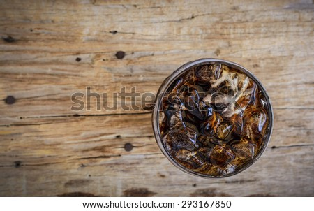 Soft drinks in glass with ice from top view on wooden floor.