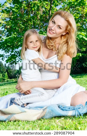Soft embrace. Young pleasant mother sitting on cover with her daughter and hugging her little daughter. - stock photo