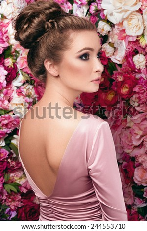 Soft facial portrait of young charming woman in rosy skin-tight gown with V-shaped cut and open back, dark smoky eyes and natural lipstick standing behind on flowered background made of peony