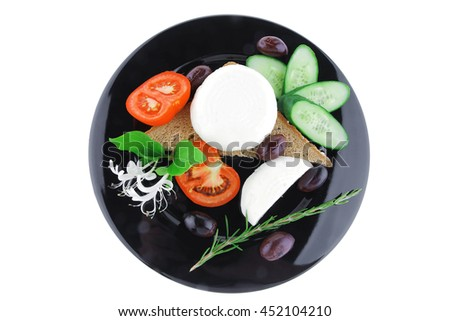 soft feta cheese on black plate with bread and vegetables - stock photo