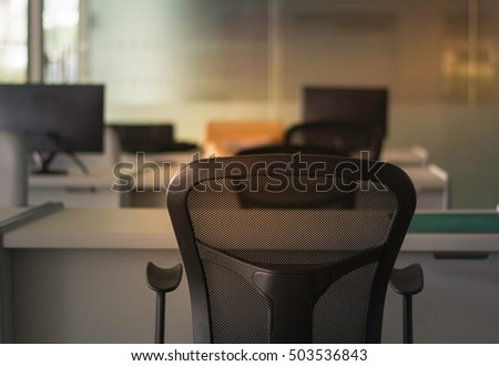 Soft focus and  Low key Black chair on blurred background modern office in morning day