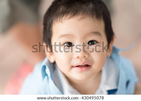 Soft focus and selective focus portrait of a happy little boy is playing on the floor in blur background (outdoors - Close-up)