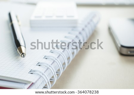 Soft focus blank notebook with pen and calculator