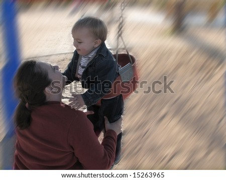 Soft focus blur of mom & son on baby swing at park - stock photo
