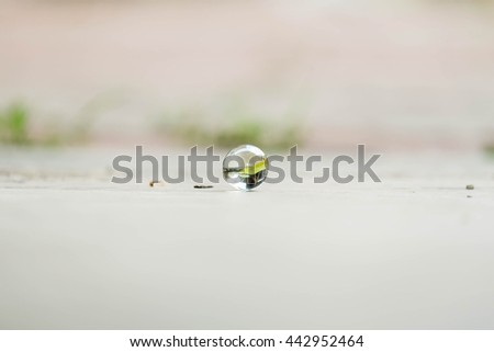 soft focus Brightly coloured glass marble with blurred background and low light
